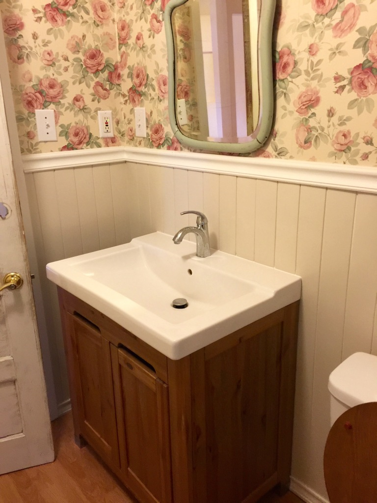 The sink and bottom of the vintage mirror in the guest bathroom.