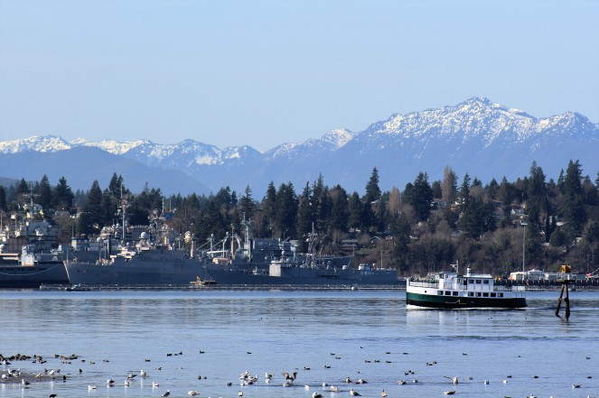 Carlisle II, one of Port Orchard's foot ferries, approaching the naval ships at Naval Base Kitsap - Bremerton, with the Olympic Mountain range looming in the distance.